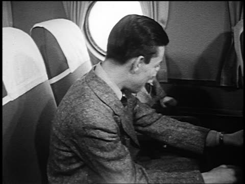 b/w 1951 two boys taking map out of pocket on back of airliner seat - 1951 stock videos & royalty-free footage