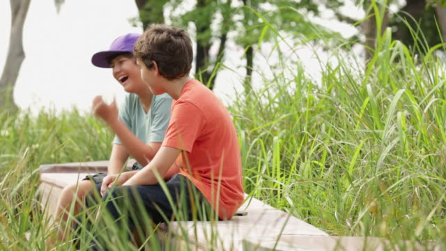 ms two boys talking and hanging out in a park. - bambini maschi video stock e b–roll