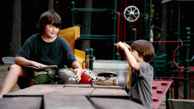 MS Two boys (10-11) talking, holding skateboards on table at playground / Lynnwood, Washington State, USA