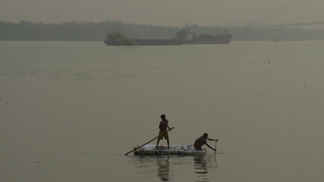 two boys use a pole and a paddle to propel their raft to the shore of the hooghly river. - hooghly river stock videos & royalty-free footage