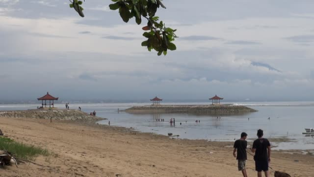 WS of two boys walking dog on Sanur beach Bali with families playing in the low tide and three Bales in mid shot The water is shallow because of the...