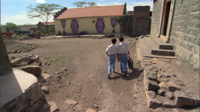 WS Two boys walking hand in hand towards village school, Pune, Maharashtra, India