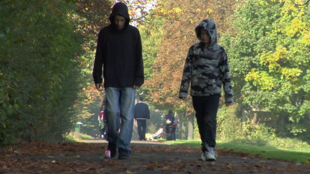 ws two boys walking in park, throwing litter, and kicking can along path / london, england - hooded top stock videos & royalty-free footage