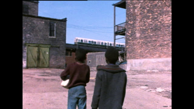 two boys watch elevated train passing through poor area; 1971 - elevated train stock-videos und b-roll-filmmaterial