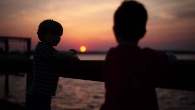 Two boys watch the colorful sky and rippling ocean from a boardwalk.