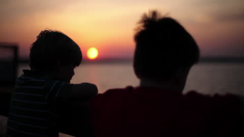 two boys watch the colorful sky from an ocean dock. - brother stock videos & royalty-free footage
