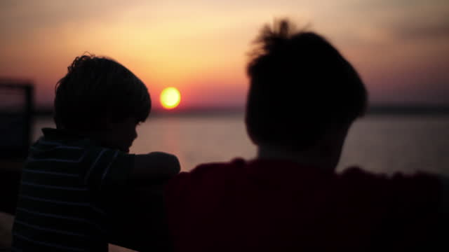 two boys watch the colorful sky from an ocean dock. - silhouette stock videos & royalty-free footage