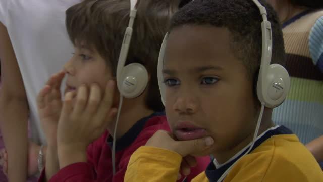 CU, Two boys (6-7) wearing headphones in computer lab