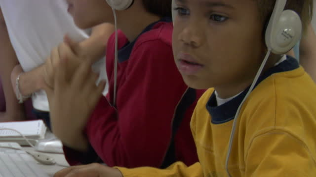 cu, tu, td, two boys (6-7) wearing headphones  using computers in computer lab - nur jungen stock-videos und b-roll-filmmaterial