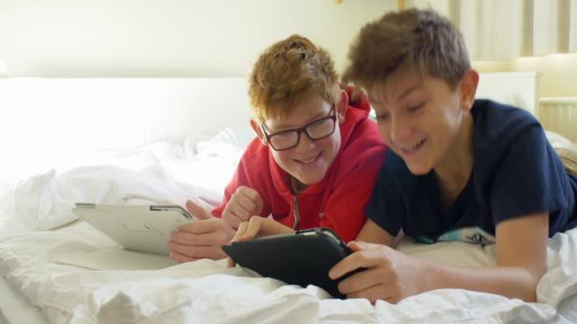 zwei jungs (12 und 11 jahre alt) mit digitalen tablet-computer - 12 13 years stock-videos und b-roll-filmmaterial