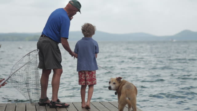 MS Two boys with grandfather and dog, fishing on dock at lake / WOLFEBRO, NH, USA