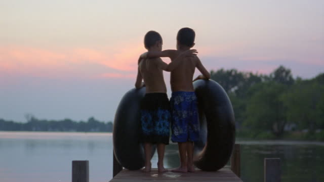 two boys with inner tubes on pier looking at pond w/ arms around each other at dusk / long pond, ny - teich stock-videos und b-roll-filmmaterial