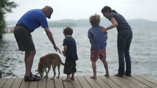 ms two boys with mother, grandfather and dog, fishing on dock at lake / wolfebro, nh, usa - grandson stock videos & royalty-free footage