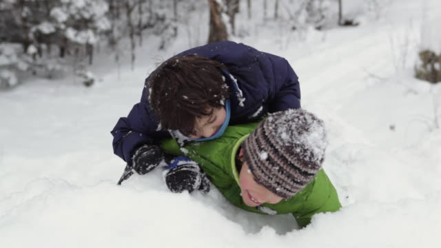 stockvideo's en b-roll-footage met ms two boys (4-9) wrestling on snowy hill, older boy pushing younger off little hill / franconia, new hampshire, usa - ski jack