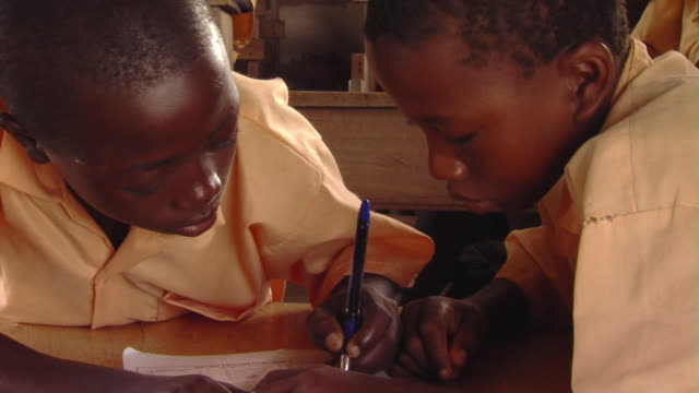 CU TD Two boys writing on paperback book sitting at desk, Tamale, Ghana