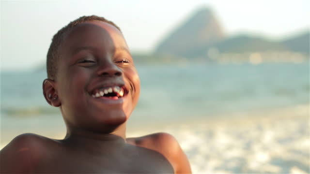 Two Brazilian boys smile at the camera and laugh hysterically on Botafogo Beach