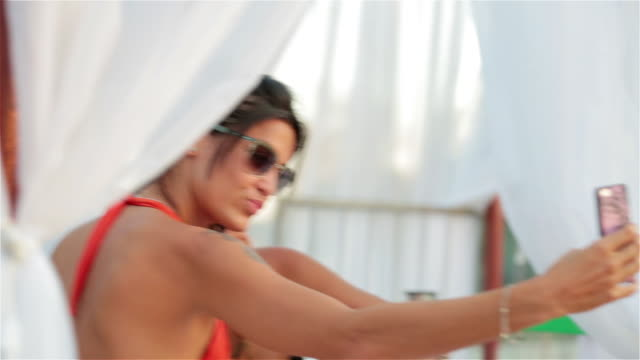 two brazilian girls pose for smartphone selfie at exclusive poolside club - exklusiv stock-videos und b-roll-filmmaterial