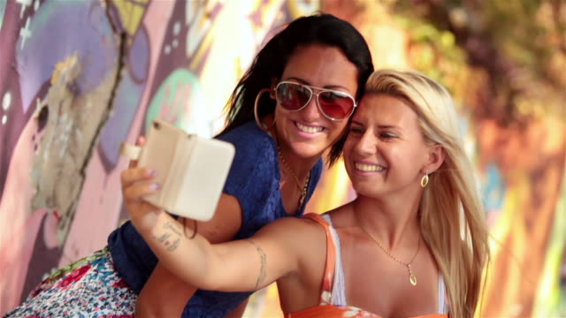 Two Brazilian girls take smartphone selfie by colorful wall graffiti in Rio