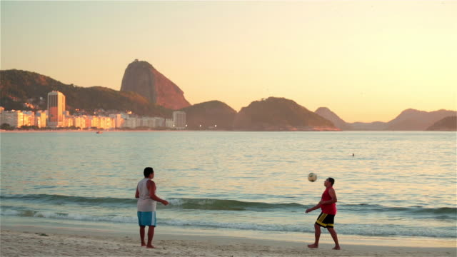 Two Brazilian men volley soccer ball back and forth by the water on Copacabana Beach
