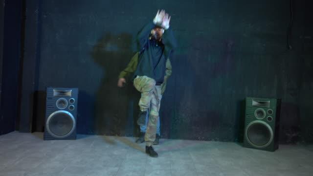 two break dancers performing in basement - attività acrobatica video stock e b–roll