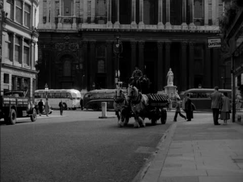Two brewery horses pull a dray past Saint Pauls Cathedral 1950s