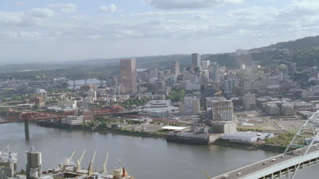 two bridges extend over willamette river as a helicopter files over the water and the city of portland, oregon. - fiume willamette video stock e b–roll