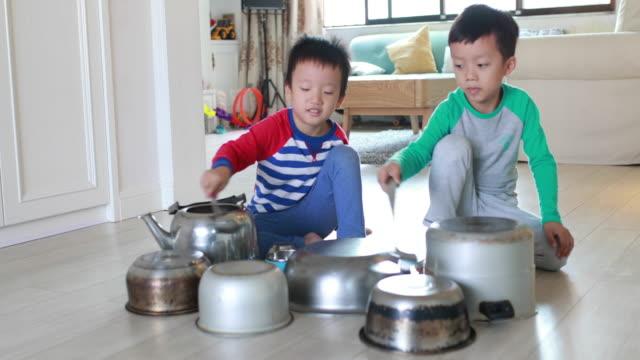 stockvideo's en b-roll-footage met twee broer spelen op verdieping met potten en pannen - in kleermakerszit