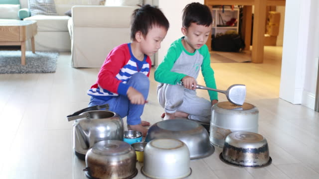 two brother playing on floor with pots and pans - drum percussion instrument stock videos and b-roll footage