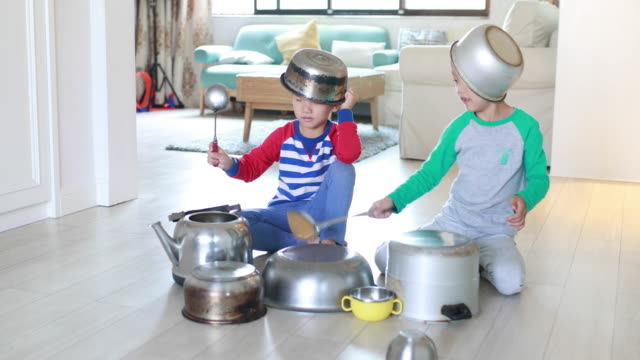 two brother playing on floor with pots and pans - kitchen stock videos & royalty-free footage