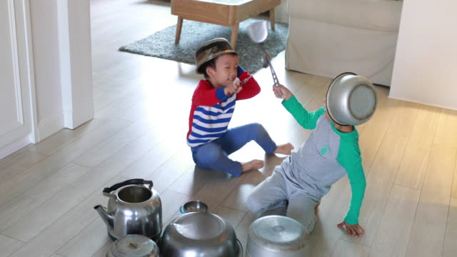 two brother playing on floor with pots and pans - pavimento video stock e b–roll