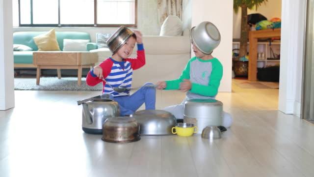 Zwei Bruder spielt im Stock mit Töpfen und Pfannen