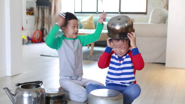 two brother playing on floor with pots and pans - drummer stock videos & royalty-free footage