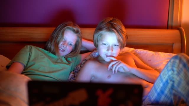 two brothers 10 and 12 watching a funny film in bed. - nackter oberkörper stock-videos und b-roll-filmmaterial
