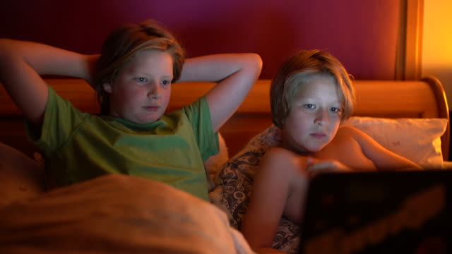 two brothers 10 and 12 watching a funny film in bed. - 10 11 years stock videos and b-roll footage