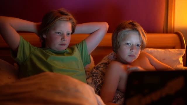 stockvideo's en b-roll-footage met two brothers 10 and 12 watching a funny film in bed. - 12 13 jaar