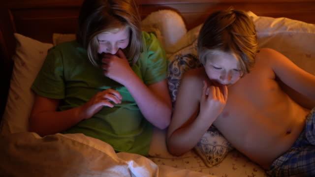two brothers 10 and 12 watching a funny film in bed. - 12 13 år bildbanksvideor och videomaterial från bakom kulisserna