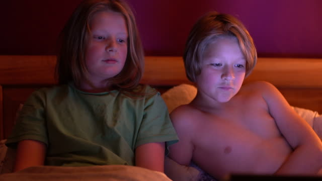 two brothers 10 and 12 watching a funny film in bed. - 12 13 år bildbanksvideor och videomaterial från bakom kulisserna