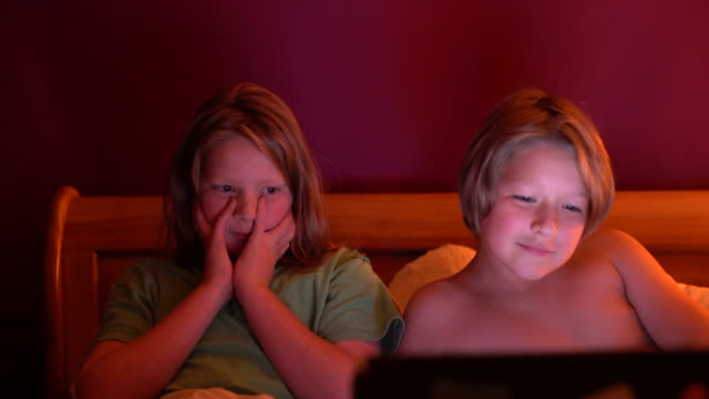 Two brothers 10 and 12 watching a funny film in bed.