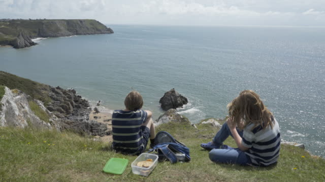 vídeos de stock e filmes b-roll de two brothers eating lunch on the top of a cliff. - país de gales