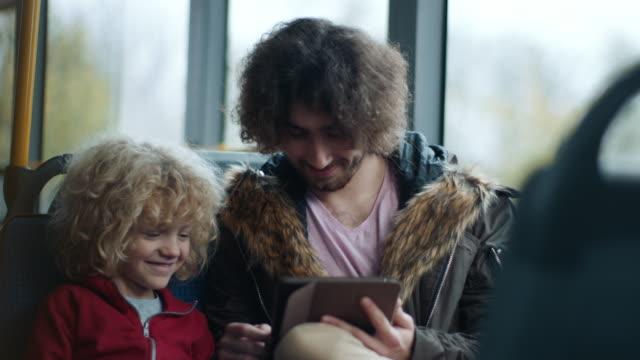 vidéos et rushes de deux frères dans le bus utilisant la tablette - monter sur un moyen de transport
