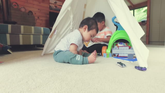 Two Brothers In House Playing With Toys And One Is Sitting Under The Tent.