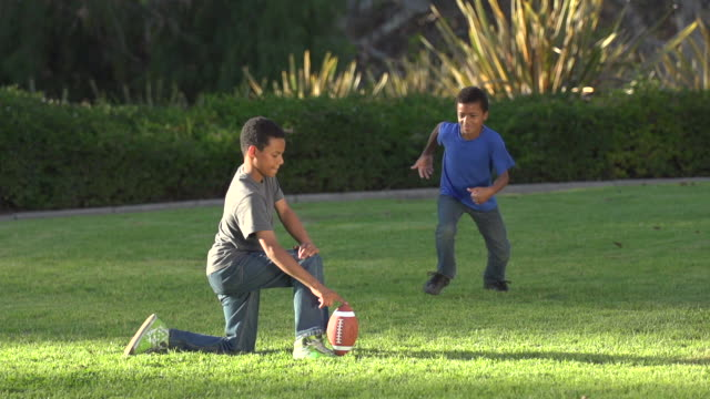 Two brothers kicking a football. - Super Slow Motion - filmed at 240 fps