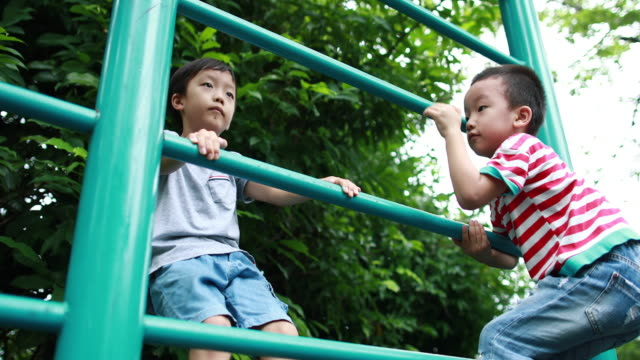two brothers play in the park - clambering stock videos & royalty-free footage