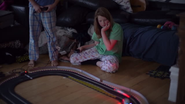 Two brothers playing with Slot Cars in real time at night.