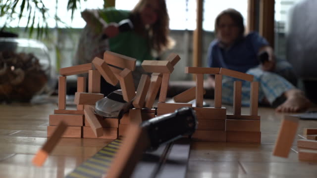 Two brothers playing with Slot Cars in Slow-motion, crashing them through some wooden blocks.