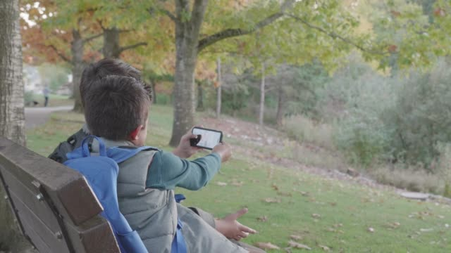 Two Brothers Sitting on a Park Bench while Taking a Selfie