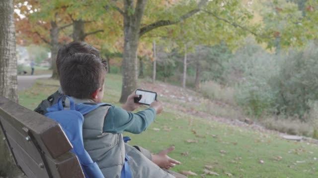 Deux frères assis sur un banc de parc, tout en prenant un Selfie