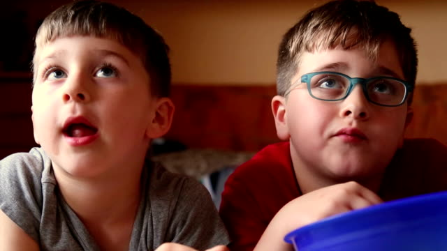 two brothers watching tv and nibbled snacks - snack stock videos & royalty-free footage