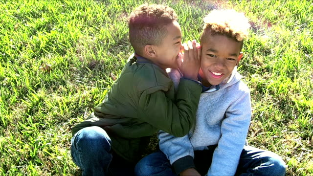 two brothers whispering in each other's ears, laughing - family with two children stock videos & royalty-free footage