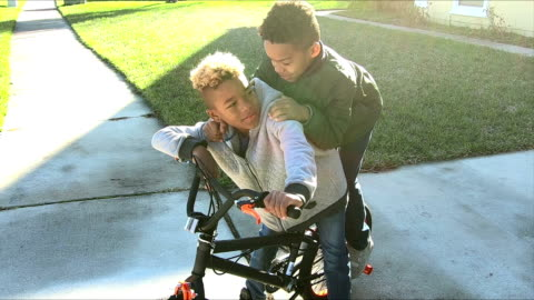 two brothers whispering in each other's ears, on bike - brother stock videos & royalty-free footage